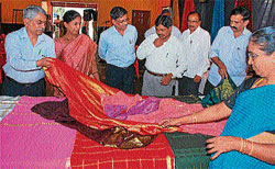 EXPO: ZP CEO S T Anjan Kumar, Madhura M S and others have a look at the silk sarees that were on display at Seetharamanjaneya temple, in Hassan on Monday. DH PHOTO
