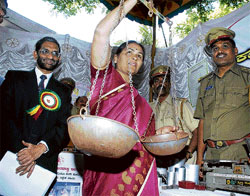 WEIGHTS AND MEASURES: Minister for Food and Civil Supplies Shobha Karandlaje tries her had at weighing, while Secretary Food and Civil Supplies B A Harish Gowda looks on at the World Consumer Rights Day-2011 in Bangalore, on Tuesday. KPN