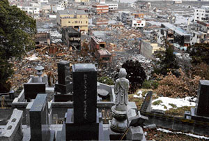 Town becomes graveyard: The devastated town of Otsuchi in Iwate prefecture appears behind tombstones on Thursday, six days after a major earthquake and tsunami hit the northeastern coast of Japan. AFP