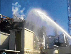 A fire truck sprays water at No 3 reactor of the Fukushima Daiichi nuclear power plant in Tomioka, Fukushima prefecture, in this image taken from a video by the Self Defence Force Nuclear Biological Chemical Weapon Defence Unit on Friday. Reuters