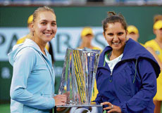 Sania Mirza (right) and  Elena Vesnina with their trophy at Indian Wells. AP