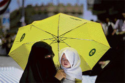 An anti-government protester and her daughter shelter under an umbrella to avoid the sun during a demonstration demanding the resignation of Yemeni President Ali Abdullah Saleh, in Sana'a, on Monday. AP