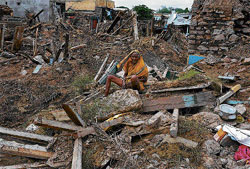 File photo of an aged woman sitting shattered in the debris of her flood-ravaged home in Talmari, Raichur district.