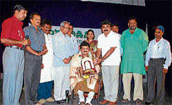 Theatre personality Mandya Ramesh being felicitated at a programme organised as part of World Theatre Day, in Chamarajanagar on Sunday. Former MLA S Balaraj, K Venkatraj and others are seen. DH photo