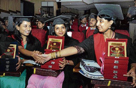 Golden girls (L) D P Shruthi (four medals) of Government Dental College, Bangalore and (R) Zulfin Shaikh (five medals) of SDM College of Dental Sciences and Hospital, Dharwad greet each other as Roopashree (five medals) of Yenepoya Medical College, Mangalore looks on at the 13th convocation of Rajiv Gandhi University of Health Sciences at the Nimhans convention hall in Bangalore on Wednesday. DH photo