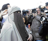 Brewing row: Kenza Drider, a niqab veiled woman from Avignon, who has become the media symbol of France's tiny community of niqab wearers, is surrounded by mediapersons  during an unauthorised protest in Paris on Monday. AFP