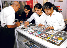 Volunteers try to assist a philatelist looking for a particular stamp on Mahatma Gandhi.