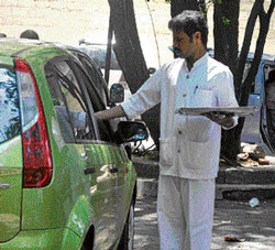 no longer popular A waiter serves food to customers at a parking lot. DH Photo