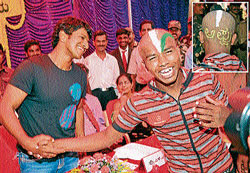 Puneeth Rajkumar shaking hands with an excited fan who had tonsured head and painted 'Appu',  his nick name at a programme held at Maharaja's college in Mysore on Friday.  dh photo