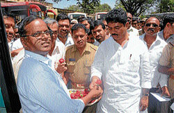 Welcome: Home and Transport Minister R Ashoka welcoming a passenger to board a bus headed to Kuvempunagar as part of Bus Day celebrations, in Mysore on Monday. MUDA Chairman L Nagendra and others are also seen. DH PHOTO