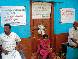 Ramya staging a dharna in front of the locked house of her husband, in Kadalamage village on Wednesday. DH photo