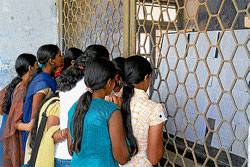 Students finding out their results by looking at the notice board at Madikeri Government              Pre University College in Madikeri on Wednesday. DH Photo