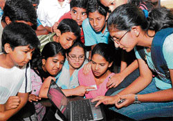With bated breath: Students check their SSLC results on a laptop at the office of the Karnataka State Secondary Education Board in Bangalore on Thursday. DH Photo