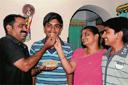 Parents giving sweets to their son Yathishchandra who scored 612 in SSLC, the highest in Chikmagalur district. DH PHOTO