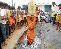 B M Nagaraju from Bethamangala enters the Agnikunda (ritual fire) carrying the Karaga, at the Gangamma Temple premises in Chikkaballapur on Saturday. DH Photo