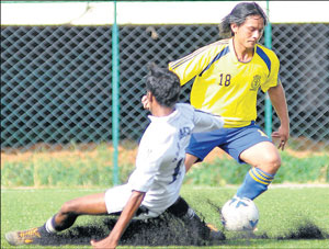 ADE's Kemal Lama (right) dribbles past Bangalore Mars' Dinesh during their State 'A' Division league match at the Bangalore Football stadium on Monday. DH PHOTO