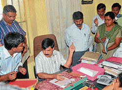 Take note: Medical Education and District In-Charge Minister S A Ramdas instructing Tahasildar Naveen Joseph to serve notice on employees, who were absent, at Town Municipal Council, in Nanjangud on Saturday. DH PHOTO