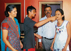 Sherwin James offering sweets to his sister Shreya Daffeny on securing first rank in architecture. Their parents Robinson Navinkumar and Serene Yashwanthi look on.
