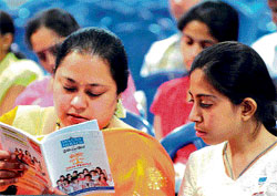 Informative A parent browses through Jnana Degula booklet at the fair. DH Photo