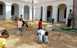On the first day...  Students of the Government Higher Primary School located on the premises of the BEO office in Kolar clean up the campus on Monday. DH PHOTO