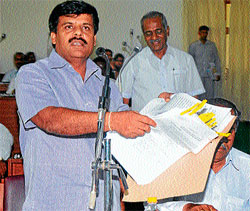 Former mayor Sandesh Swamy producing the documents, at MCC council meeting in Mysore on Tuesday. Dh photo