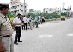A cop shows the dacoity spot near Silk Board in HSR Layout on Tuesday. DH Photos