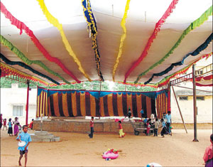 Stage being prepared for the 11th district Kannada Sahitya Sammelana at the government school ground. DH Photo