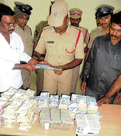 Police take stock of the cash recovered from a vehicle intercepted near Bagepalli checkpost on Saturday night. dh photo