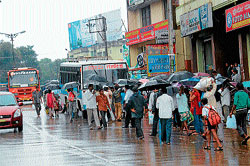 The passengers are forced to wait for the bus on the road in the absence of a proper bus shelter in State Bank area in Mangalore. DH PHOTO
