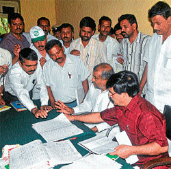 taking stock: Medical education and district in-charge minister S A Ramdas verifies records at the taluk office in Hunsur on Friday. Karnataka Housing Board (KHB) chairman G T Devegowda and other officers are seen.DH Photo