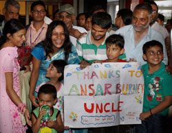 Family members of released sailors display a poster thanking Human right activists Ansar Burney at IGI Airport in New Delhi on Friday. After 10 months in the captivity of Somali pirates, six Indian sailors of M V Suez vessel reached home to an emotional welcome from family members.  PTI Photo