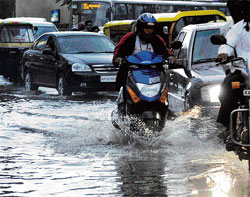 Motorists ride through the waterlogged Magarath Road in the City on Saturday. DH Photo