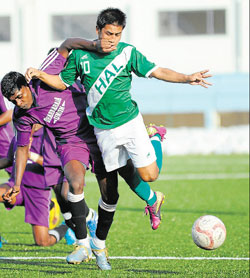 HASC's Malemngamba Meitei (right) and Madan of Dharmaraja Union  challenge each other during their Super Division clash on Sunday. DH Photo