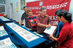 Dakshina Kannada Philatelic and Numismatic Association Vice-president Baikady Srinivasa Rao explaining about miniature sheets during the exhibition of stamps and coins at Mangalore Head Post Office on Sunday.
