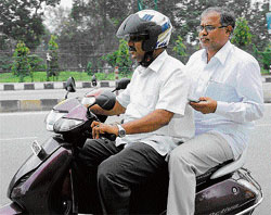 Former minister Suresh Kumar rides pillion on a friend's scooter on Sunday. dh Photo