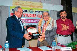 Madras Institute of Development Studies former director V K Nataraj being felicitated by Mangalore University Vice Chancellor Prof T C Shivashankara Murthy in Mangalore University on Thursday. Registrar Chinnappa Gowda looks on.