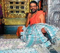 Shiroor Mutt seer Lakshmivaratheertha exhibiting a garland made of ` 50 and `100 currencies to be given to Hulivesha participants during Vitlapindi mahotsava scheduled to be held on August 22. DH Photo
