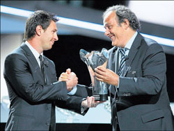 UEFA president Michel Platini hands over the UEFA Best Player in Europe award to Barcelona's Lionel Messi during the Champions League draw ceremony in Monaco on Thursday. AFP