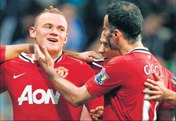 GOLDEN BOY Wayne Rooney is congratulated by Javier Hernandez and Ryan Giggs after scoring his third goal in Manchester United's 5-0 win over Bolton on Saturday. reuters