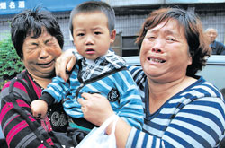 victims of madness: A child cries with his grandmother Ding Lou (left), after his father Zhai Guoqiang and mother Li Congli were killed by a 'mad' man in Gongyi, Henan province, China on  Wednesday. reuters