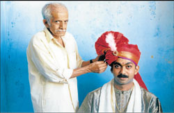 Prabhakar Rao helping a groom wear his handmade 'Peta'.