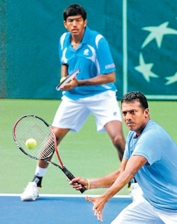 Mahesh Bhupathi (foreground) volleys as partner Rohan Bopanna watches on during their doubles tie against Japan on Saturday. AP