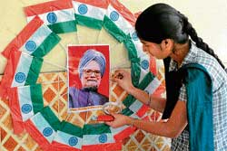 A schoolgirl places a photo of Prime Minister Manmohan Singh on a wall in the middle of circle formed by Tricolour to celebrate his 79th birthday in Amritsar on Monday. AFP