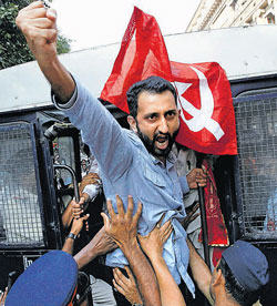 Police detain a Left-wing activist protesting on Dalal Street, in Mumbai, on Friday. PTI