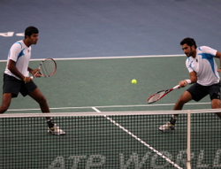 Pakistani Aisam-Ui-Haq Qureshi (R) near teammate Indian Rohan Bopanna hits a return to French Nicolas Mahut and French Julien Benneteau during their double final of the Paris Tennis Masters Series indoor tournament on November 13, 2011 at the Bercy Palais-Omnisport (POPB) in Paris. AFP