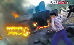 A grab from an amateur video shows a boy throwing an object at a vehicle as a tank burns in Daraa on Monday. AP