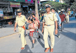 Rescue: Police personnel escort students, returning from school, to safety at Ramaswamy Circle as lawyers stage a rasta rokho in Mysore on Tuesday. AFP