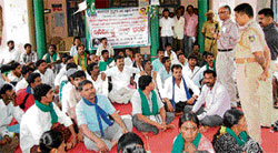 Tahsildar T A Hanumantharaya and Circle Inspector Srinivasamurthy speak to the protesters in front of the Bagepalli TMC on Tuesday. DH photo