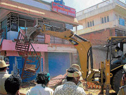 Law and order: Malur Town Municipal Council personnel bring down unlawfully  constructed buildings on the main road using earthmovers on Tuesday. DH photo