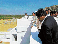 Restart: Dr B C Mylarappa, Bangalore University registrar on Monday inspects the post-graduation centre building near Mangasandra in Kolar taluk, the construction of which had been stalled. dh photo
